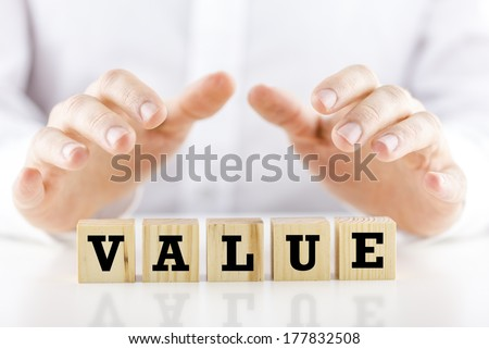 Conceptual image of a businessman in shirtsleeves holding his hands protectively above a line of wooden cubes with the word - Value. - stock photo