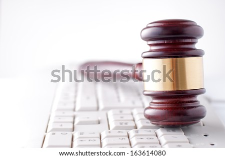 Conceptual image of a gavel used by a judge or auctioneer with a brass band around the head lying on a computer keyboard - stock photo