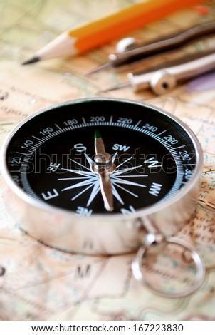 Conceptual image of a magnetic compass and pencil lying on a map for plotting a journey, geocaching or orienteering where it is used as a navigational instrument - stock photo