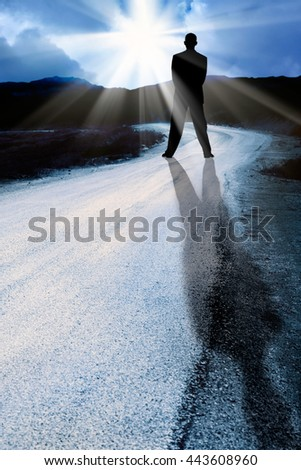 conceptual image of a man standing agains the sun rays - stock photo