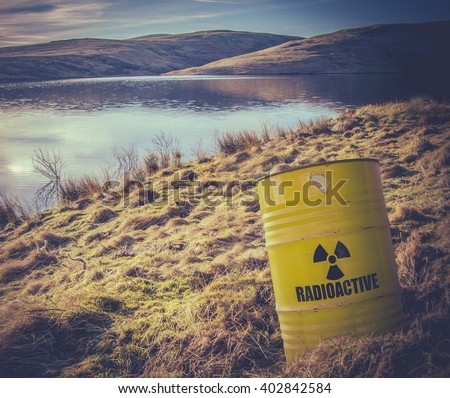 Conceptual Image Of A Radioactive Nuclear Waste Barrel Or Drum Near Water In The Countryside - stock photo