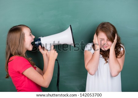 Conceptual image of a schoolgirl making herself loudly heard by using a megaphone close to another girl, who tries to ignore her by covering her ears, or in pain