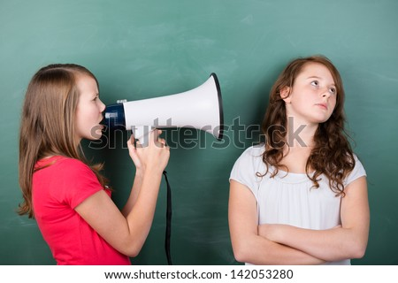 Conceptual image of a schoolgirl trying to make herself heard by using a megaphone close to another girls ears, who ignores her - stock photo