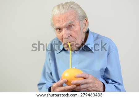 Conceptual image of a senior man holding a whole grapefruit drinking the fresh grapefruit juice through a straw in a healthy diet and nutrition concept