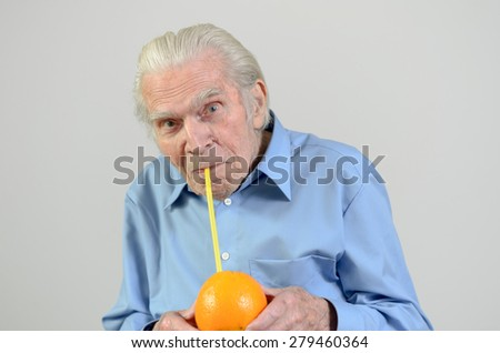 Conceptual image of a senior man holding a whole orange drinking the fresh orange juice through a straw in a healthy diet and nutrition concept