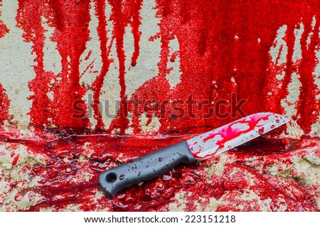 Conceptual image of a sharp knife with blood on it resting on a concrete floor. Concept photo of murder and crime