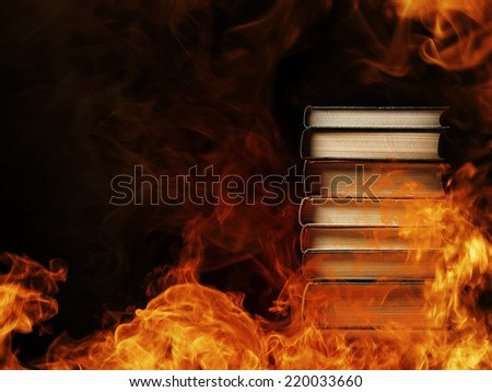 Conceptual image of a tall stack of hardcover books in a burning fire with flames and smoke swirling around them in a darkened room with copyspace - stock photo