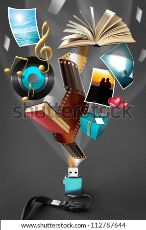 Conceptual image of a tiny USB drive where a large amount of multimedia files and documents can fit in - stock photo