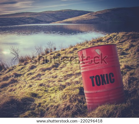 Conceptual Image Of A Toxic Waste Barrel Or Drum Near Water In The  Countryside - stock photo