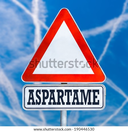 Conceptual image of a triangular white traffic warning sign with the word - Aspartame - a non-saccharide articifial sweetener which has long been debated over safety concerns, blue sky with contrails. - stock photo