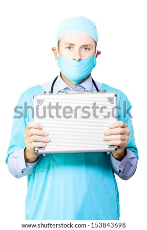 Conceptual image of a young male surgeon in a mask and gown holding up a small metal case signifying an organ donation or transplant - stock photo