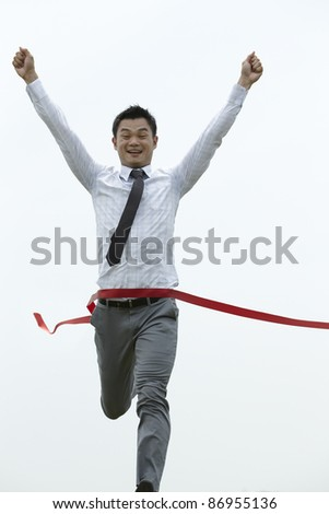 Conceptual image of an Asian Business man winning a race - stock photo