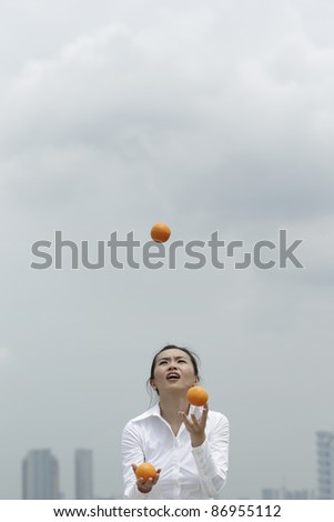 Conceptual image of an Asian Business woman juggling oranges - stock photo