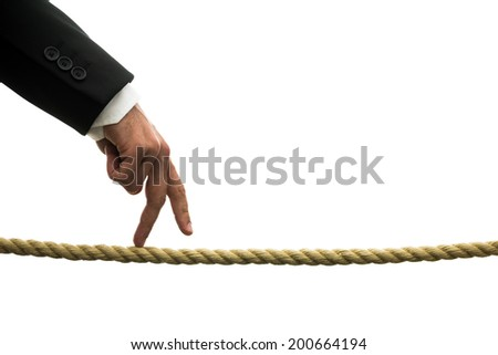 Conceptual image of business determination with a businessman walking his fingers along a length of rope or a tightrope with perseverance and determination to succeed against all odds - stock photo