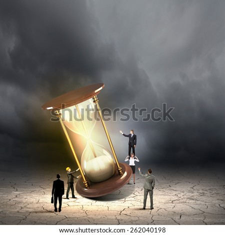 Conceptual image of business people looking at sandglass - stock photo