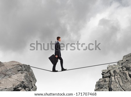 Conceptual image of businessman walking on rope above gap