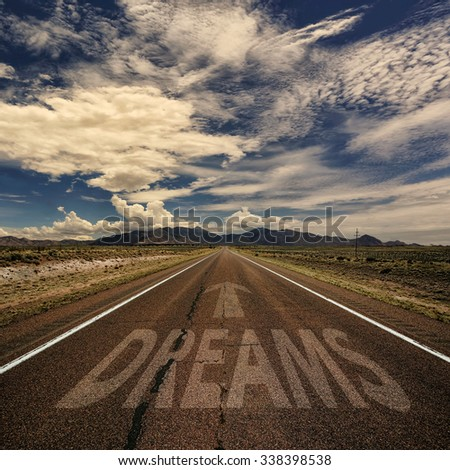 Conceptual image of desert road with the word dreams and arrow - stock photo