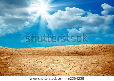 conceptual image of dried and cracked landscape over dramatic sky.