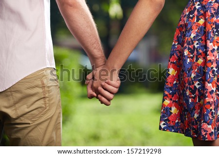 Conceptual image of female and male holding by hands