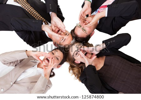 Conceptual image of four businesspeople with their heads together looking directly down at the camera isolated on white