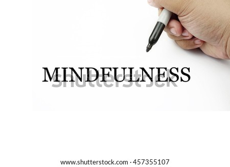 Conceptual image of handwriting MINDFULNESS with the hand and pen isolated in white background.