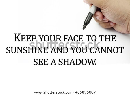 Conceptual image of handwriting quotes KEEP YOUR FACE TO THE SUNSHINE AND YOU CANNOT SEE A SHADOW with the hand and pen isolated in white background. copy space . Quotes concept.