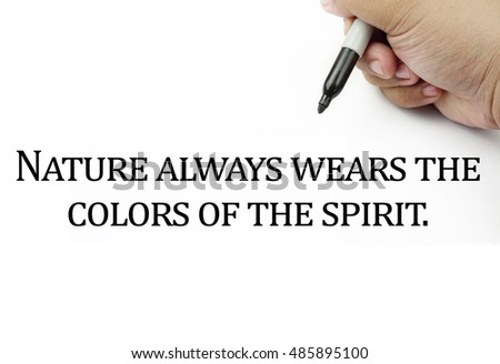 Conceptual image of handwriting quotes NATURE ALWAYS WEARS THE COLORS OF THE SPIRIT with the hand and pen isolated in white background. copy space . Quotes concept.