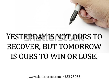Conceptual image of handwriting quotes YESTERDAY IS NOT OURS TO RECOVER,BUT TOMORROW IS OURS TO WIN OR LOSE with the hand and pen isolated in white background. copy space . Quotes concept.
