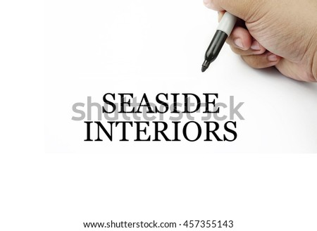Conceptual image of handwriting SEASIDE INTERIORS with the hand and pen isolated in white background.