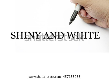 Conceptual image of handwriting SHINY AND WHITE with the hand and pen isolated in white background.