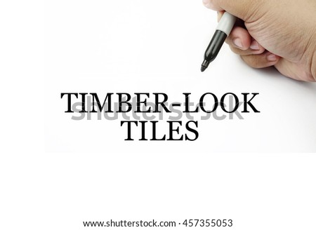 Conceptual image of handwriting TIMBER-LOOK TILES with the hand and pen isolated in white background.