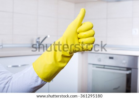 Conceptual image of home cleaning. Close up of human hand with yellow rubber glove showing ok sign with thumb up. Clean kitchen countertop and furniture in background