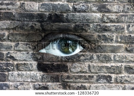 Conceptual image of human face with open eye covered with stone wall texture - stock photo