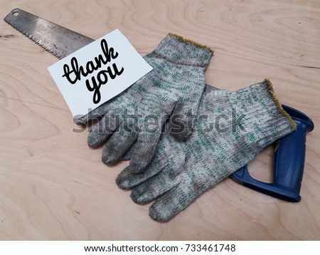conceptual image of paper note word - THANK YOU with dirty glove/saw on the wooden table.