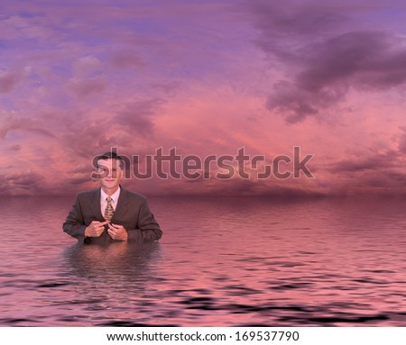 Conceptual image of senior businessman in suit up to waist in deep water. Man is looking proud and confident and the sunset reflects an image of success and not drowning in problems - stock photo