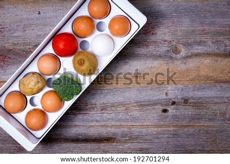 Conceptual image of storage and management of food in the refrigerator with a view from above of a plastic egg tray with eggs, broccoli, tomato, kiwifruit and a potato on a wooden table with copyspace - stock photo