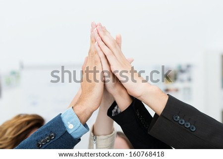 Conceptual image of teamwork and cooperation with a group of business people raising their hands and placing them together, close up view of their hands - stock photo