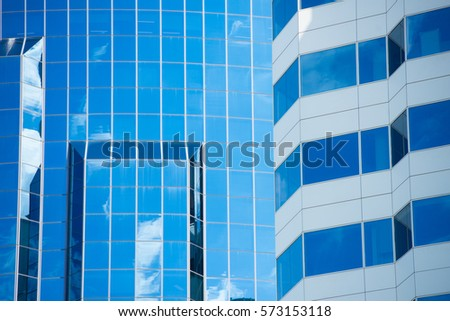 Conceptual image of textured facade of modern design skyscraper office buildings in downtown business district, reflection in window surface pattern background and copy space.