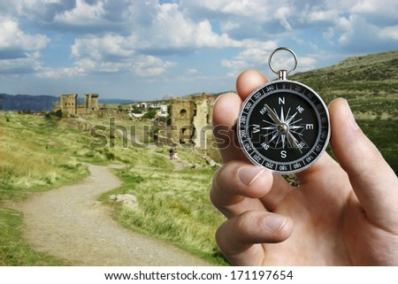 Conceptual image of the hand of a man using a compass to navigate and find the direction while sightseeing abroad with the ruins of an ancient castle in the background - stock photo