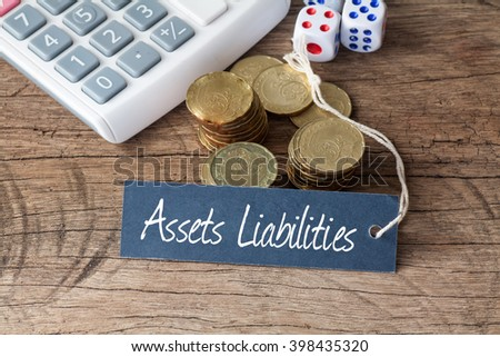 Conceptual image of the words Assets Liabilities written on label tag with coins,dice and calculator - stock photo