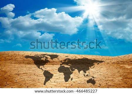 conceptual image of world map on dried cracked landscape over sky. Furnished NASA image used for this image.