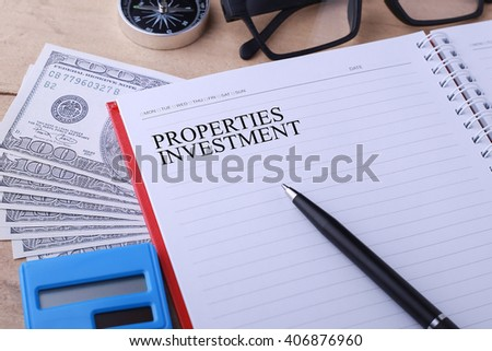 Conceptual image. PROPERTIES INVESTMENT words. Calculator, hundred dollar bills, pen, notebook, glasses and compass on wooden table. - stock photo