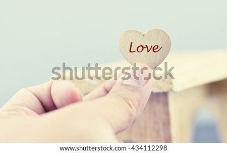conceptual image,romantic look hand holding heart made from wood with word LOVE over blurred and selective focus background - stock photo