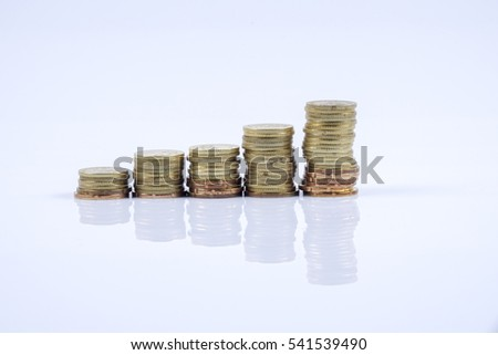 Conceptual image. Stacks of coins against white background . Copy space.