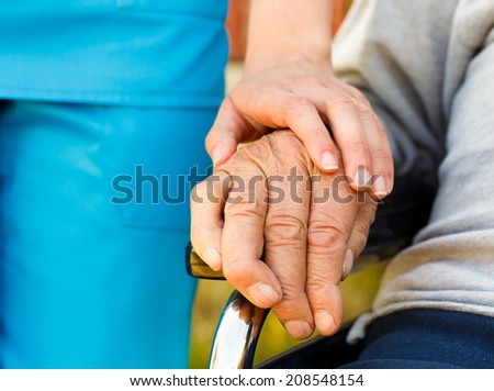 Conceptual image - support for the elderly in wheelchair. - stock photo