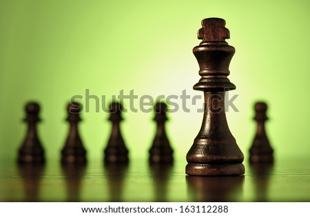 Conceptual image with a close up view of a wooden king chess piece with a row of blurred pawns in the background against green with copyspace - stock photo