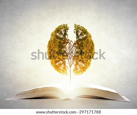 Conceptual image with green tree growing from book - stock photo