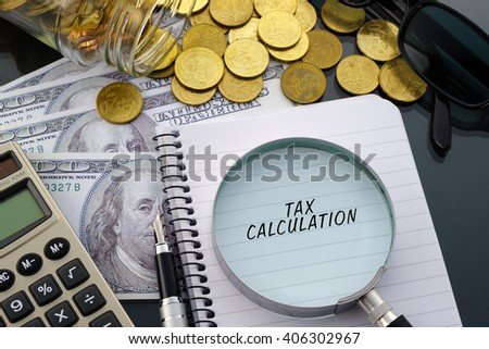 Conceptual image with hundred dollar bills, coins, calculator, notepad and magnifying glass with word Tax Calculation.