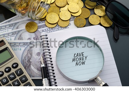 Conceptual image with hundred dollar bills, coins, calculator, notepad and magnifying glass with word Save Money Now. - stock photo