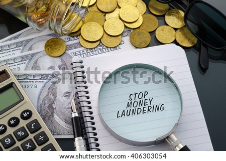 Conceptual image with hundred dollar bills, coins, calculator, notepad and magnifying glass with word Stop Money Laundering. - stock photo